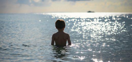 Яжмамка с ребенком на пляже.